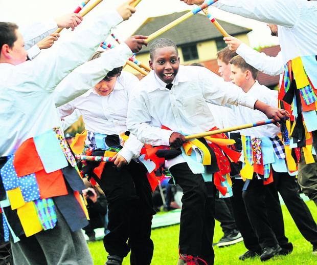 Pelumi Maxwell, 10, from Pegasus School stick dances through an arch created by fellow pupils