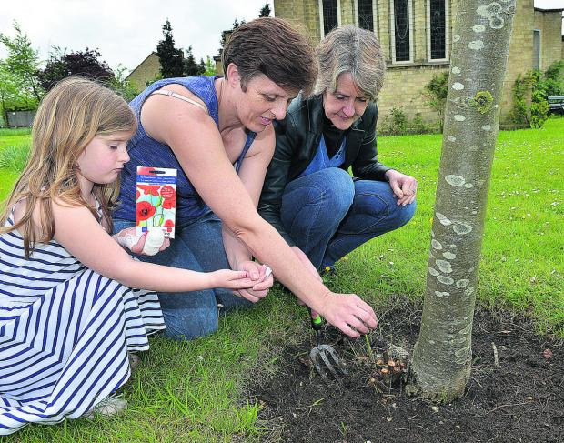 Scarlet Trafford, five, and her mum Michelle Trafford help the Rev Maggie Thorne plant poppy seeds at the church