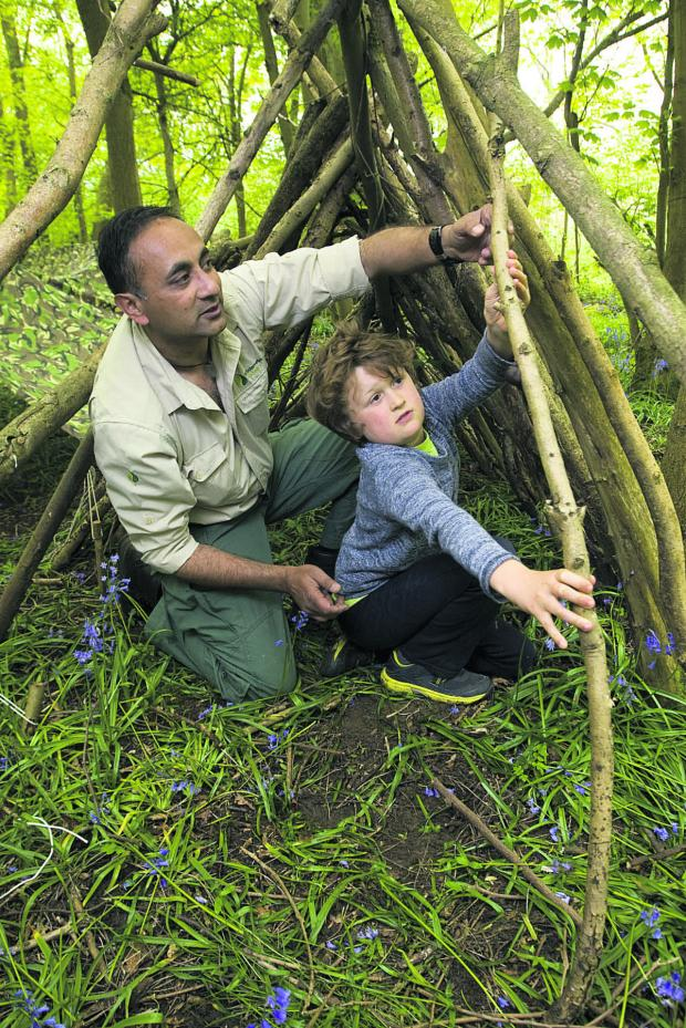 thisisoxfordshire: Manse Ahmad teaches Francis Garcia Shapley how to build a shelter        Picture: OX66981 Antony Moore