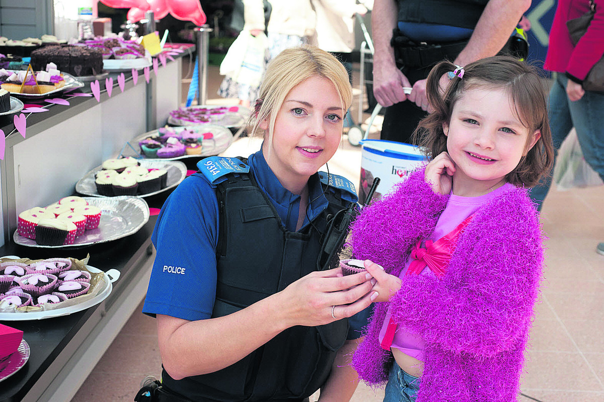 PCSO Kate Hellenburgh with three-year-old Sapphire Field at the police cake sale