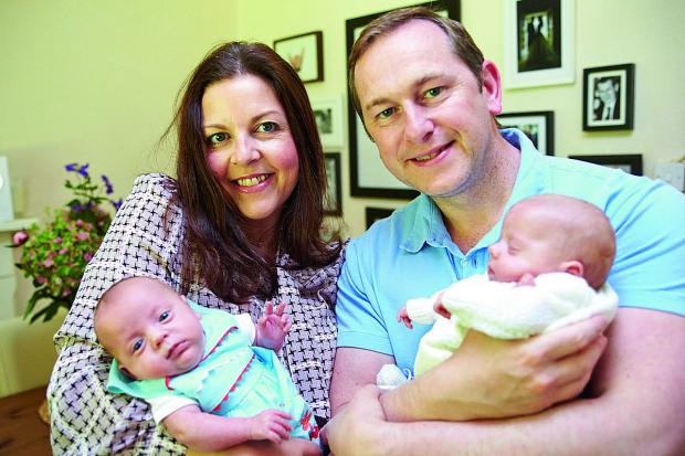 thisisoxfordshire: Julie and Drew Brown hold their 14-week-old twin daughters Beaux, left, and Scarlett, right, at their home. The couple are doing an abseil to raise money for the hospital that saved their daughters, who were born at just 26 weeks     Picture: OX67729