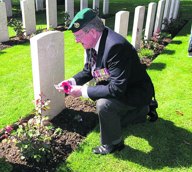 Joe Beardsley laying a poppy at the grave of his friend Cpl Gerald Dean