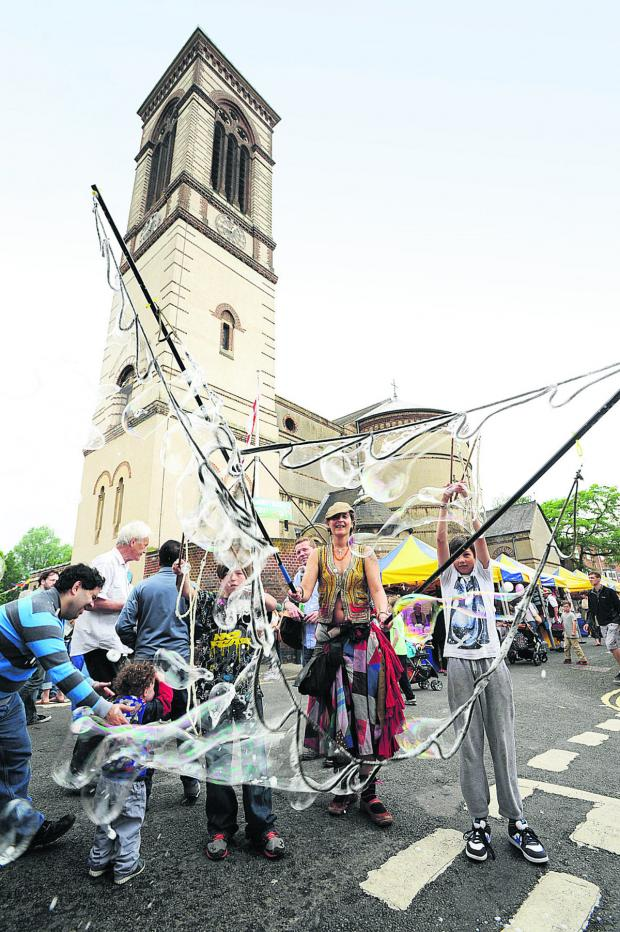 thisisoxfordshire: Lara Love creates some giant bubbles in front of St Barnabas Church during Jericho Street Fair