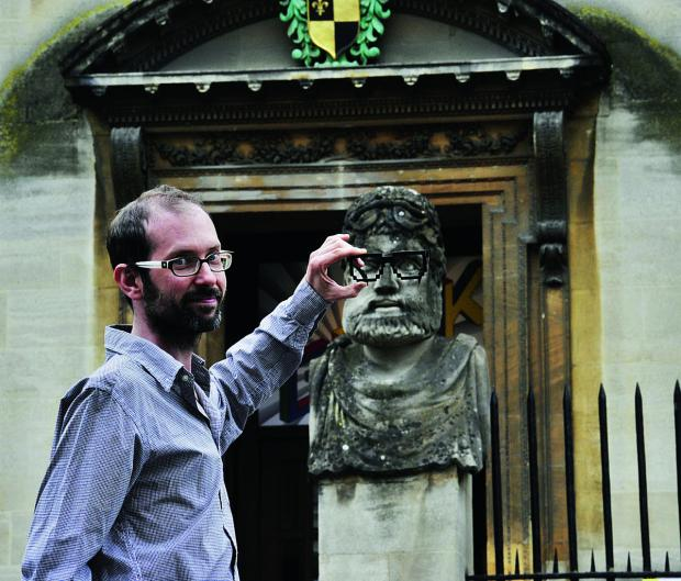 thisisoxfordshire: Scott Billings of the Museum of Science in Oxford shows where the Geek Specs had been placed – the new pair come courtesy of digital technology. The specs have been stolen from the two stone heads outside the building and there is an appeal for their sa