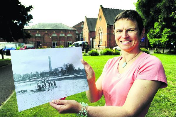 thisisoxfordshire: Oxford historian Liz Woolley with a photo showing the old waterworks buildings, with the now South Oxford Community Centre behind her. Picture: OX68386 David Fleming