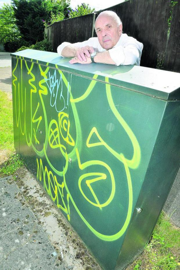 thisisoxfordshire: Cumnor Parish Council chairman Brian Stops with graffiti on the corner of Arnolds Way and Cumnor Hill. Picture: OX68409 Simon Williams