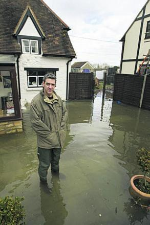 Adrian Porter in his South Hinksey garden, left, at the height of the February floods