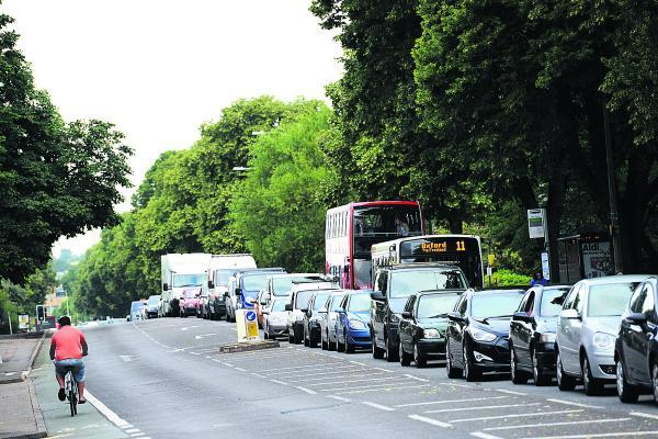 Traffic queueing to get into Oxford on Botley Road yesterday morning as a cyclist pedals out of the city. Picture: Leah McLaren