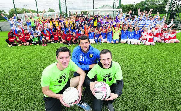 Oxford United goalkeeper, Max Crocombe, centre, and tournament organisers, Dale Harris, left, and Andrew Baker, with players and officials who took part in the event. Pictures: OX68485 Damian Halliwell