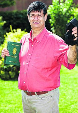 Dr Taj Hargey, director of the Muslim Educational Centre of Oxford holding a burka and a copy of the Quran