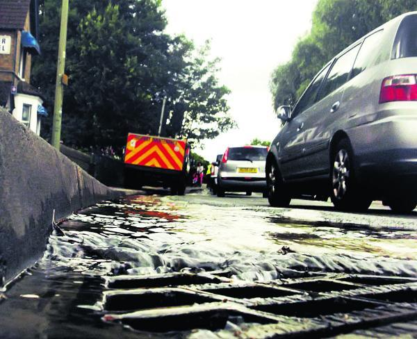 thisisoxfordshire: Cars drive through the water leak on Botley Road in Oxford. Picture: Neil Braggins