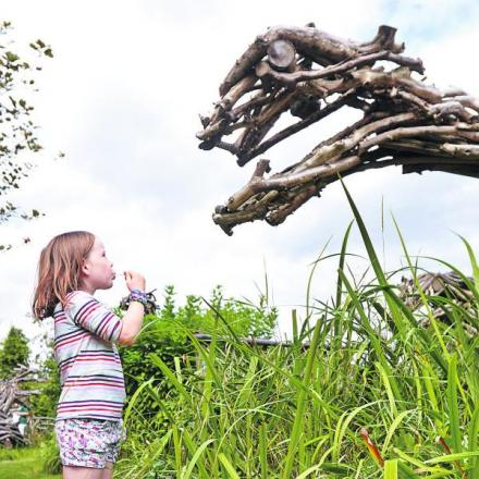 Mae Lovell, six, looks at one the dozens of dinosaur sculptures made from driftwood created in the allotments