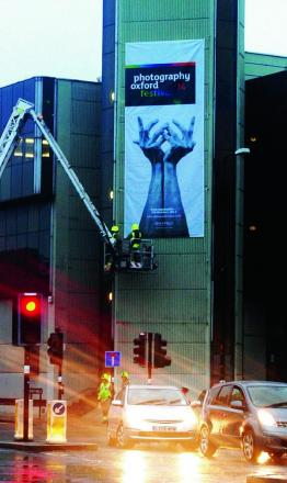Firefighters hang the banner facing Frideswide Square