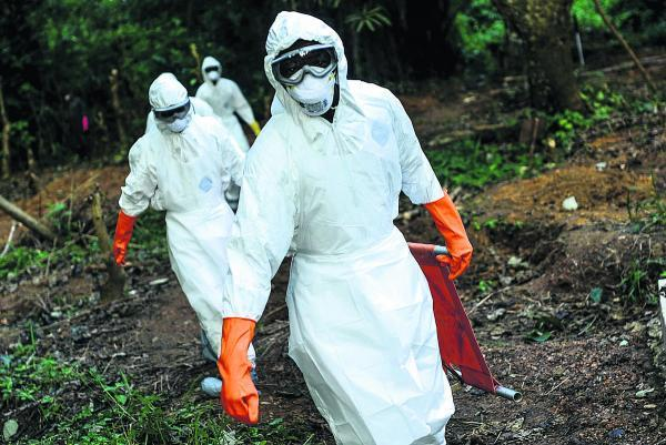 Members of a volunteer medical team wear special uniforms for the burial of seven people who died of Ebola in Kenema, Sierra Leone, on Tuesday