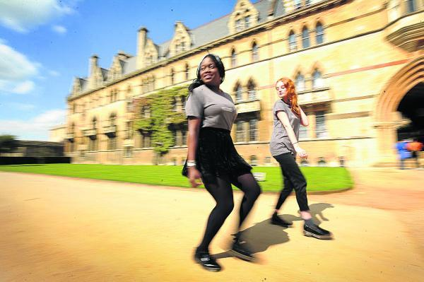 Annette Theu, right, and Chelsea Battle pictured outside Christ Church, are walking backwards around all the Oxford University colleges to raise money for an upcoming trip to Togo with the charity Y Care International