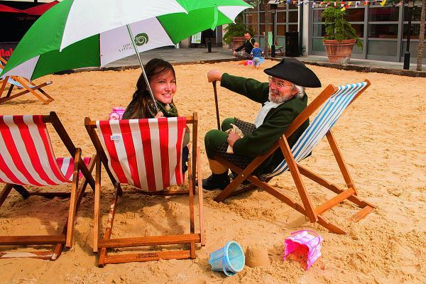Ian Giles takes time out from his role as Oxford Castle Unlocked guide Daniel Harris to relax on the beach with Sam Pace, Oxford Castle Quarter operations manager