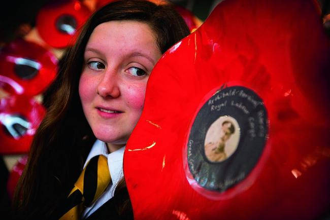 Twelve-year-old Maisie Harris with a poppy made from a vinyl record dedicated to her great-great-grandfather Archibald Harris.		Picture: OX71019 Damian Halliwell