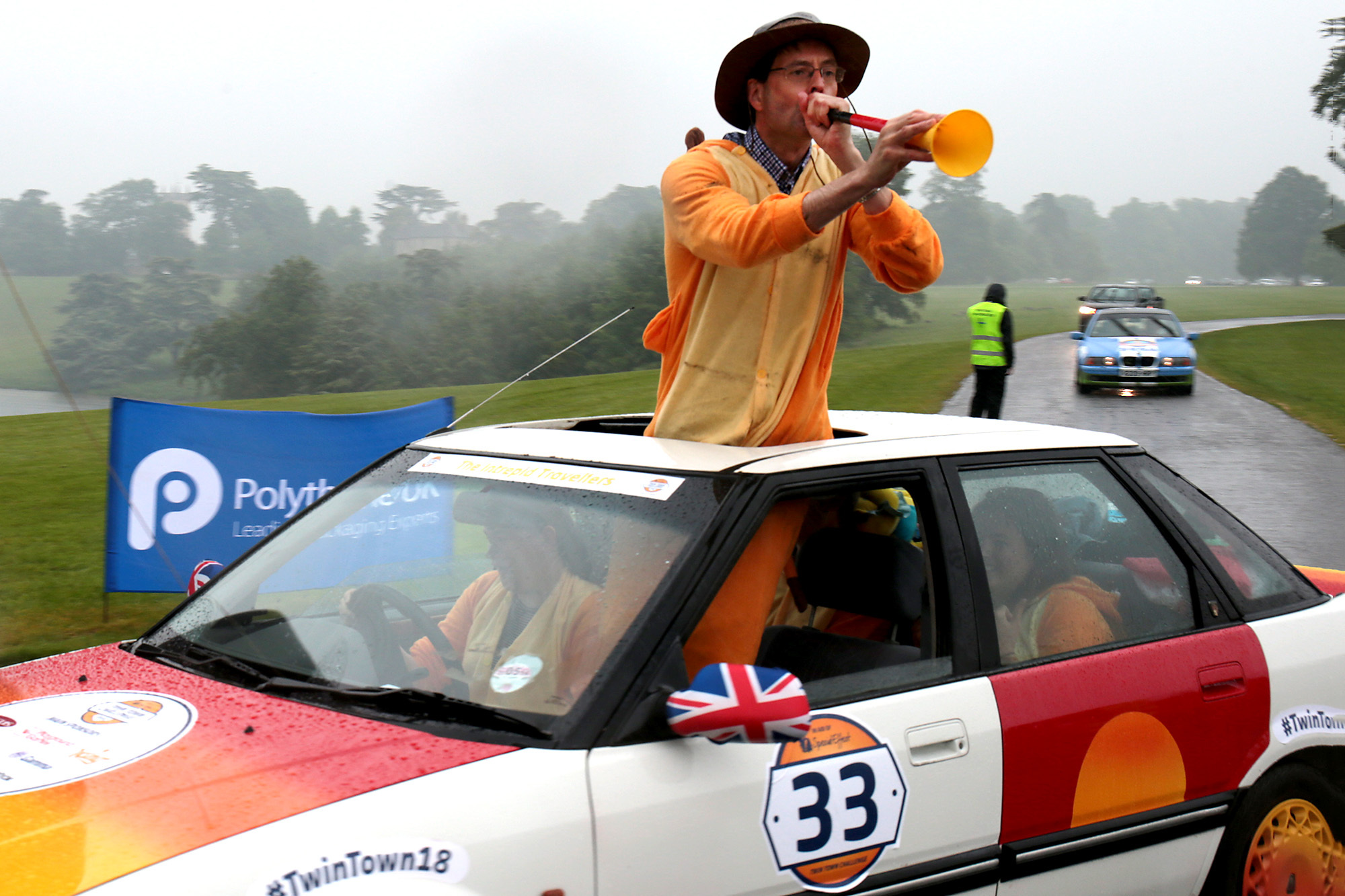 Jonathan Longden from the Intrepid Travelers team sounds his vuvuzela as the 100 cars in the Twin Town Challenge 2018 set off fom Blenheim Palace