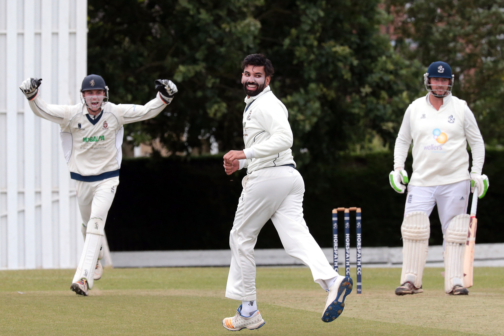 MIXED EMOTIONS: Thame Town's Hassam Mushtaq and wicket-keeper Callum Russell celebrate as Horspath batsman Robbie Eason shows his despair at edging to Will Sutcliffe in the slips Picture: Ric Mellis