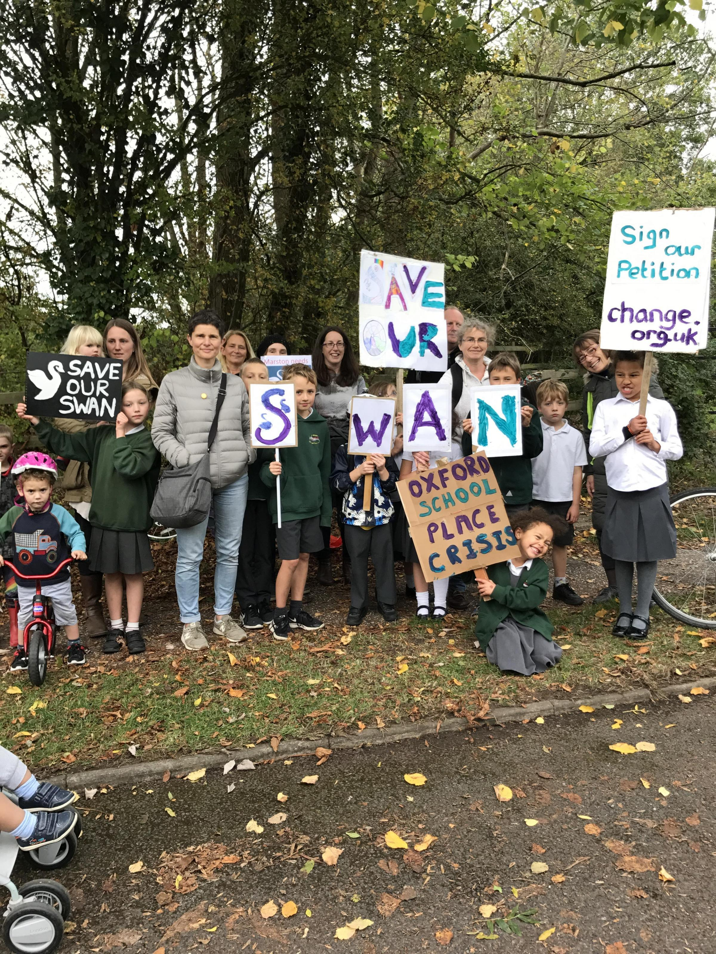 Pro-Swan School families gathered on Marston Ferry Road on Monday afternoon to lobby for approval